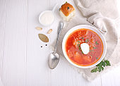 Red borscht soup in white bowl