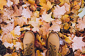 Casual unisex boots with autumn fallen leaves