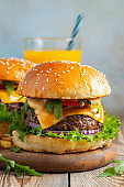 Two fresh homemade burgers with fried potatoes and orange juice on a wooden table