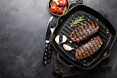 Closeup ready to eat steak Top Blade beef breeds of black Angus with grill tomato, garlic and on a wooden Board. The finished dish for dinner on a dark stone background. Top view with copy space