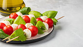 Caprese salad - skewer with tomato, mozzarella and basil, italian food and healthy vegetarian diet concept on a light background. with copy space