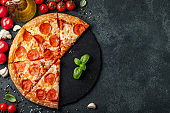 Tasty pepperoni pizza and cooking ingredients tomatoes basil on black concrete background. Top view of hot pepperoni pizza. With copy space for text. Flat lay