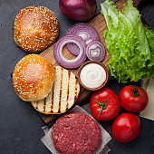 Hamburger Building Kit. Fresh ingredients for Burger on dark stone table. Top view