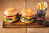 Close-up of delicious fresh home made burger with lettuce, cheese, onion and tomato on a rustic wooden board. Also fries and Cola with ice on a wooden table