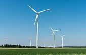 Wind power generators in front of a clear blue sky