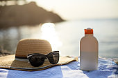 Suntan cream bottle and sunglasses on beach towel with sea shore on background. Sunscreen on deck chair outdoors on sunrise or sunset. Skin care and protection concept. Golden tan