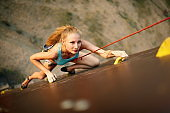 Strong woman and business success concept. Young caucasian pretty woman practicing climbing on artificial rock wall outdoors. Slim sporty blonde training speed bouldering session