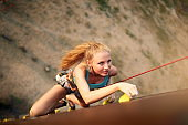 Strong woman and business success concept. Top view of young caucasian pretty woman practicing climbing on artificial rock wall outdoors. Slim sporty blonde training speed bouldering session