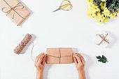 Flat lay arrangement female's hands tying gift box