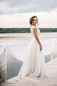 Beautiful bride stands on the pier