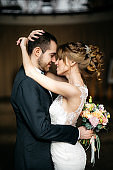 Young and beautiful bride and groom embrace