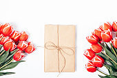 Gift box tied with rope among summer red flowers