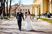 Newlywed couple bride and groom photoshoot after wedding ceremony in Saint-Petersburg Russia. White wedding dress with long veil and classical black suit or smoking with bowtie. Businessman in glasses