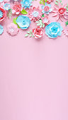Blue and pink paper flowers on the pink background