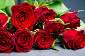 Bouquet with red roses on the rustic background