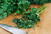 Freshly chopped up bunch of parsley on wood chopping board next to kitchen knife.
