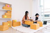 Freelancer asian women teamwork sme business working at office in home interior writing address,packing order for customer and online delivery for ready packing on working table