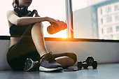 Woman exercise workout in gym fitness breaking relax holding protein shake bottle after training sport with dumbbell and headphone music equipment healthy lifestyle bodybuilding,