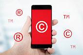 Copyright, trademark symbols flying around smartphone.