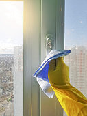 Female hand in yellow gloves cleansing window with a blue rag glass