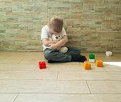 sad little boy with teddy bear sitting on the floor