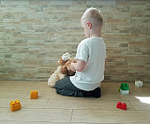sad little boy with a teddy bear sitting on the floor protesting emotions