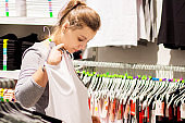 Caucasian brunette girl on shopping. A woman tries on new clothes in a fashionable boutique. Dress in shopping Center.