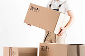 relocation services concept. Mover holding cardboard box isolated on white background. Loader in uniform carrying moving box. Delivery of parcels. Parcel delivery service.