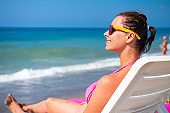 Woman relaxes on deckchair against blue sea water