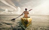 Woman traveler exploring calm tropical bay by kayak.