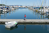 Marina with moored boats in calm blue water and small boy