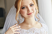 Perfect wedding day of woman bride, portrait of girl in white wedding dress in Bridal veil. Morning of the bride waiting for the groom and wedding ceremony