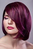 Portrait of beautiful fashion model woman with short purple colored hairstyle and makeup with calm closed eyes.