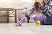 Unrecognizable woman polishing wooden floor