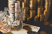 Coins in glass jar for money saving, copy space