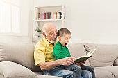 Senior man reading book for his grandchild