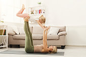 Mother and little daughter practicing acroyoga at home