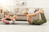 Mother and daughter doing yoga exercises at home