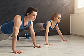 Couple making plank or push ups exercise indoors