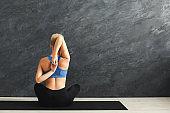 Woman training yoga in cow head pose