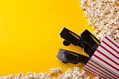 3D glasses and popcorn on yellow background