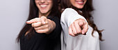 Smiling business women pointing at camera at gray background