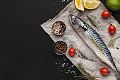 Mackerel and cooking ingredients on black background