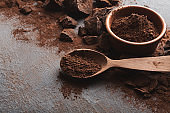 Crushed chocolate pieces and cocoa on gray background