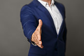 Confident businessman stretching his hand for greeting