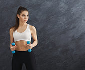 Fitness model woman with dumbbells on grey