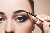 Make-up artist apply eyebrow shadow with brush, beauty