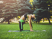 Woman training yoga in table top pose outdoors