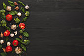 Border of fresh vegetables on wooden background