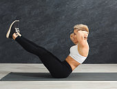 Fitness woman stretching at grey background indoors